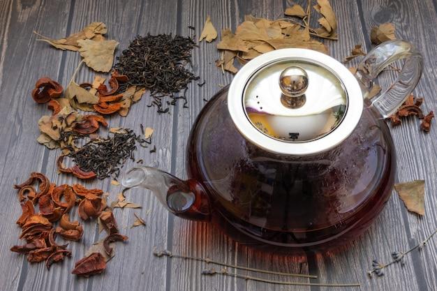 Bule com chá, em torno de alguns tipos de chá em um fundo escuro de madeira