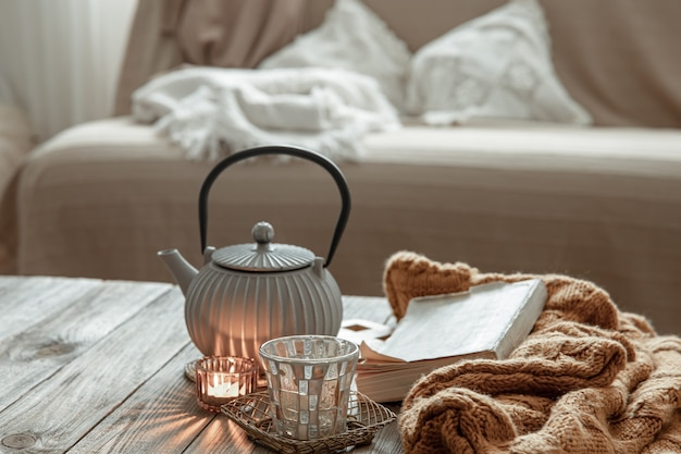 Bule com chá, peça de malha e velas em cima da mesa do interior da sala.