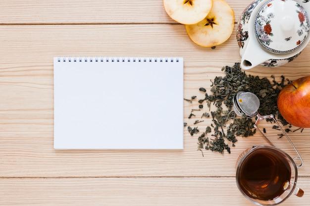 Bule com maquete de maçã e notebook