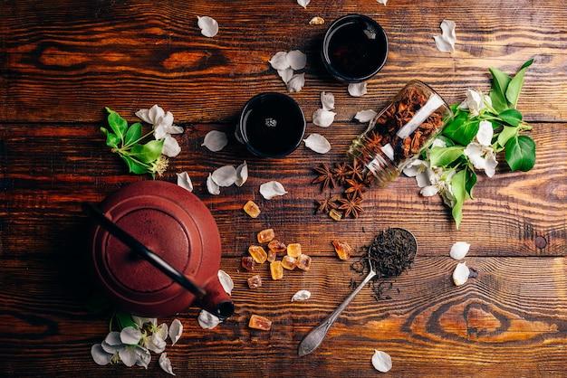 Bule com uma colher cheia de chá, flores de maçã, açúcar e estrela de anis na mesa de madeira. vista de cima.