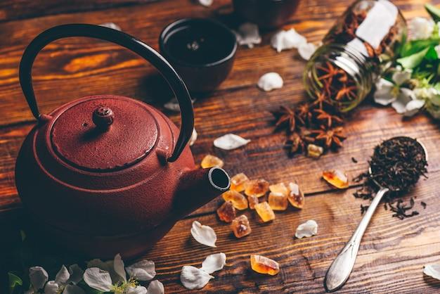 Bule com uma colher cheia de chá, flores de maçã, açúcar e estrela de anis na mesa de madeira.