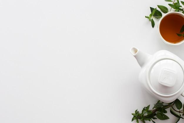Bule com uma xícara de chá e hortelã