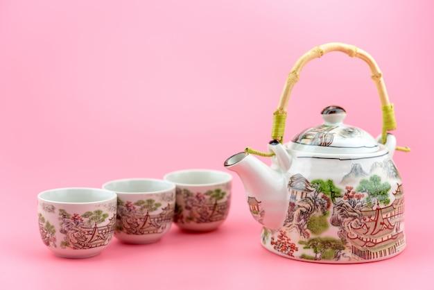 Bule com xícaras em um fundo rosa.