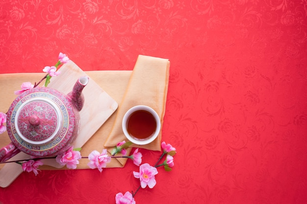 Bule, copo do chá e flor de cerejeira no fundo vermelho da toalha de mesa.