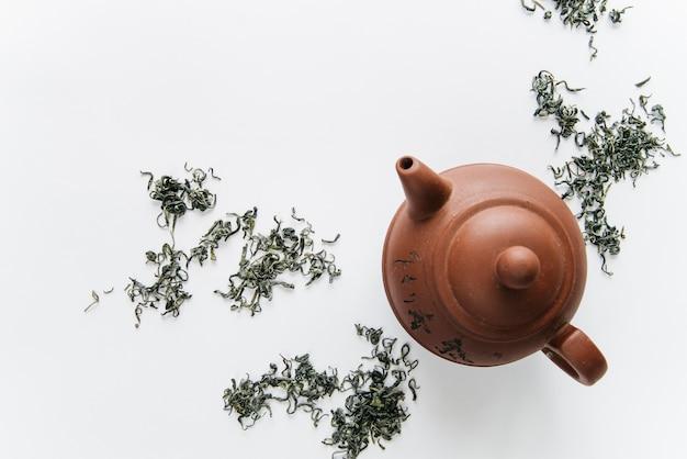 Bule de barro chinês com ervas secas, isolado no fundo branco