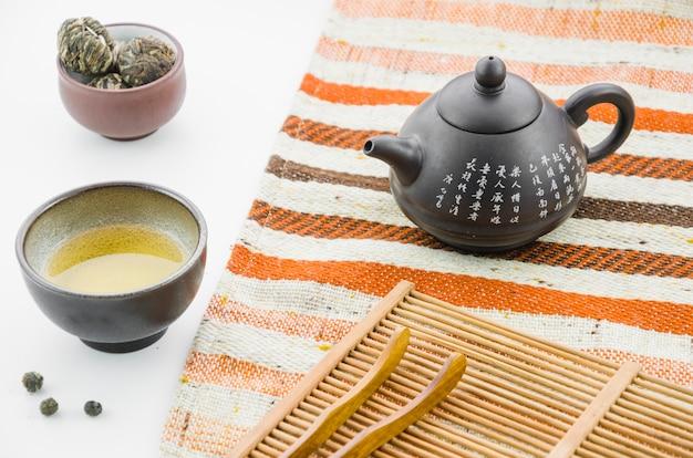 Bule de barro chinês com floral florescendo bola de chá xícara de chá contra o pano de fundo branco