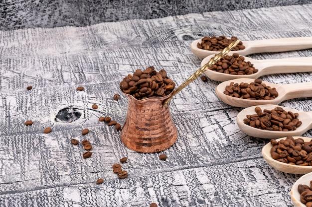 Bule de café cheio de grãos de café na vista superior de madeira