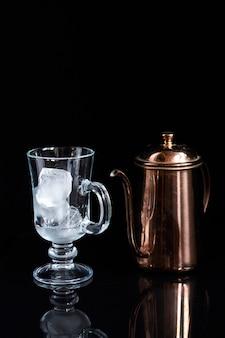 Bule de café de cobre e copo de café com leite vazio com gelo