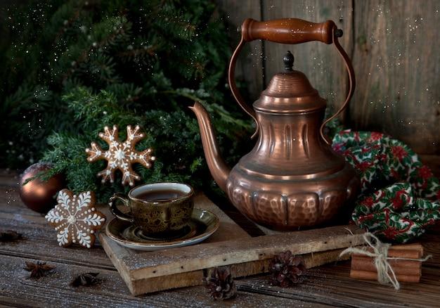 Bule de café de cobre vintage, xícara de café preto e pão de gengibre de natal.