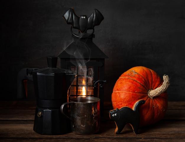 Bule de café preto, caneca com café preto, pão de mel chocolate, lanterna preta com velas e abóbora.