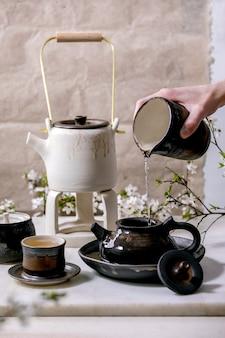 Bule de cerâmica artesanal branco e preto com mão masculina derramando água da jarra katakuchi, canecas de cerâmica, cerejeira em flor como decoração em pé na mesa de mármore. cerimônia do chá tradicional japonesa