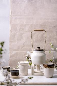 Bule de cerâmica artesanal de artesanato branco e preto com canecas de cerâmica preta, jarro katakuchi e cerejeira em flor como decoração em pé na mesa de mármore. cerimônia de chá tradicional japonesa. teadrinking