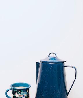 Bule de cerâmica azul e caneca em fundo branco
