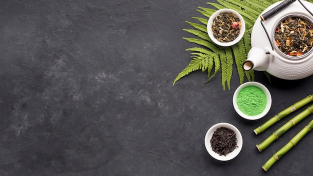 Bule de cerâmica branca e erva de chá seco com matcha chá em pó sobre fundo preto