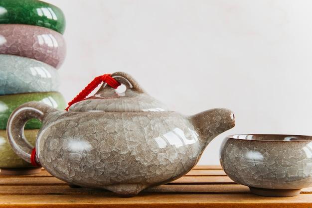 Bule de cerâmica chinesa e xícaras de chá na mesa de madeira contra a parede