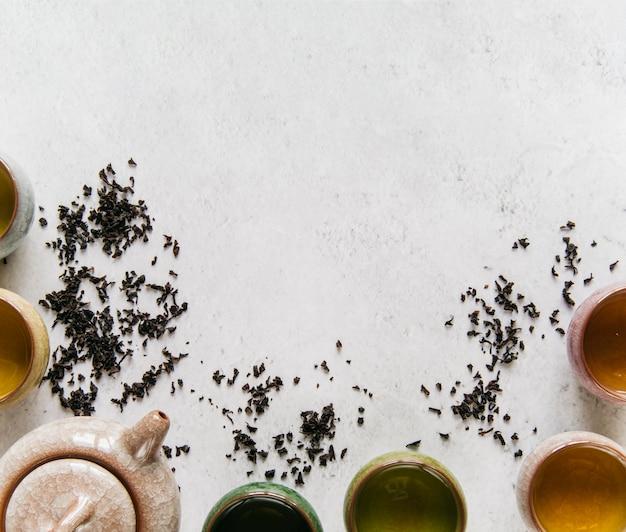Bule de cerâmica com xícara de chá de ervas em pano de fundo concreto