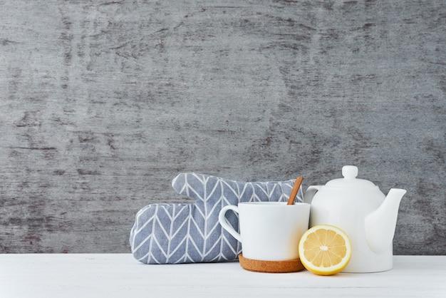 Bule de cerâmica, copo branco e limão em uma madeira