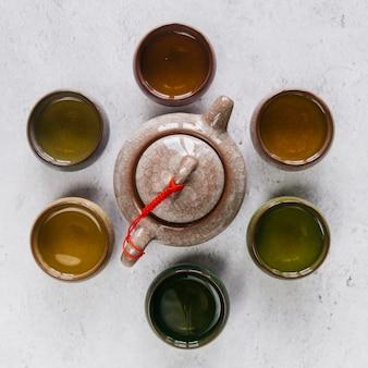 Bule de cerâmica de barro chinês rodeado de xícara de chá de ervas no pano de fundo