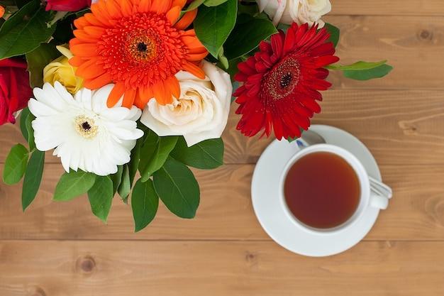 Bule de cerâmica e xícaras em uma mesa de madeira. um buquê de flores brilhantes em um vaso. café da manhã.