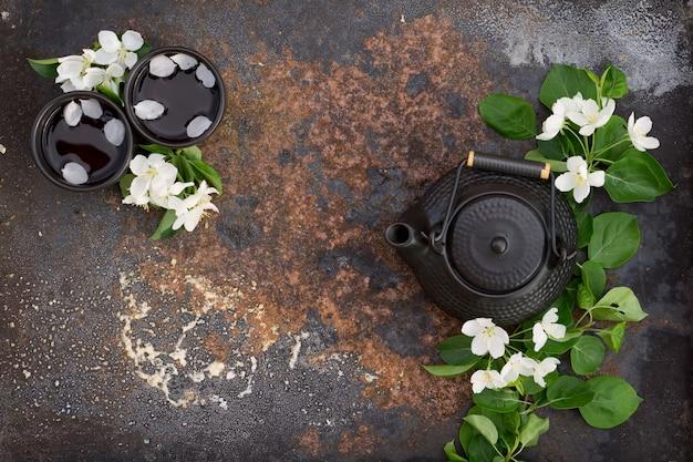 Bule de cerâmica preto e xícara com chá quente decorado por galhos de maçã flor de primavera sobre fundo de ferro rústico de textura escura.
