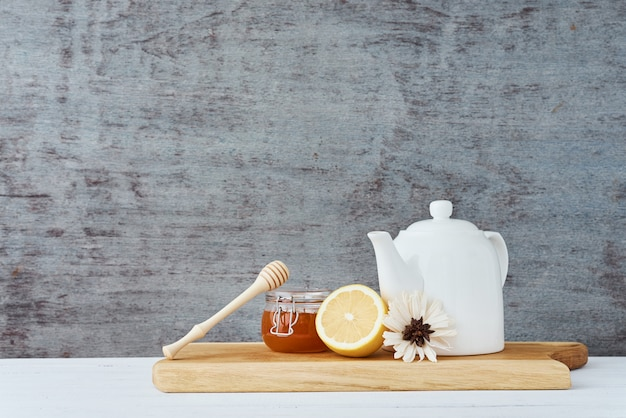 Bule de cerâmica, xícara branca, mel em uma jarra de vidro e limão na madeira
