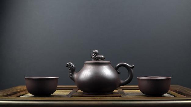 Bule de chá antigo e duas tigelas de barro em uma superfície de madeira