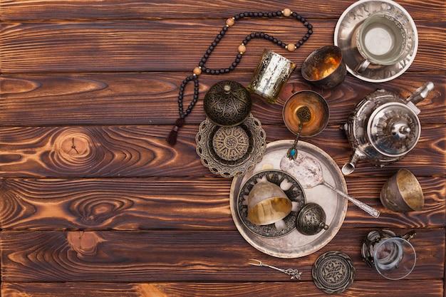 Bule de chá árabe com xícaras e miçangas na mesa