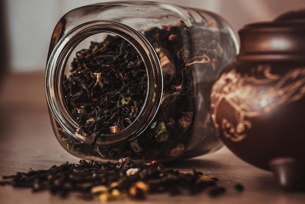Bule de chá asiático com dragão no suporte e jarra com chá de frutas espalhado