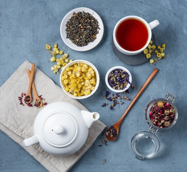 Bule de chá branco com uma xícara de chá de ervas lavanda, camomila e rosa solta na mesa azul