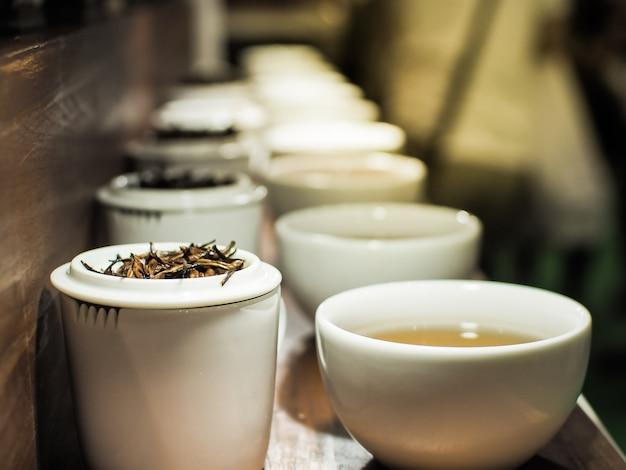 Bule de chá branco e xícaras com as folhas de chá preto