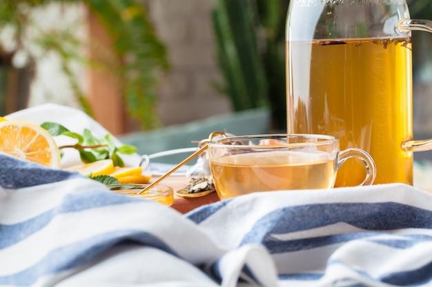 Bule de chá chinês limão gengibre mel na toalha de mesa leve