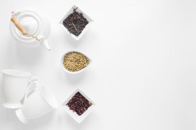 Bule de chá; copo cerâmico; flores secas de crisântemo chinês; folhas de chá secas no pano de fundo branco