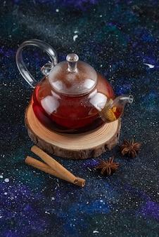 Bule de chá de vidro com canela na placa de madeira
