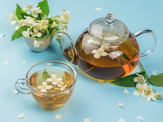 Bule de chá de vidro e copo de vidro com chá de jasmim sobre uma superfície azul. uma bebida revigorante que faz bem à saúde.