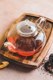 Bule de chá de vidro e folhas de chá secas na mesa