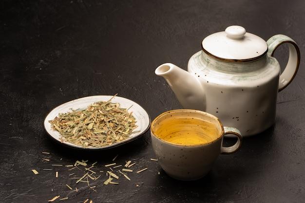Bule de chá e xícara de chá sencha. um fabricante de chá sencha está ao lado de uma xícara e bule de chá em uma mesa preta.