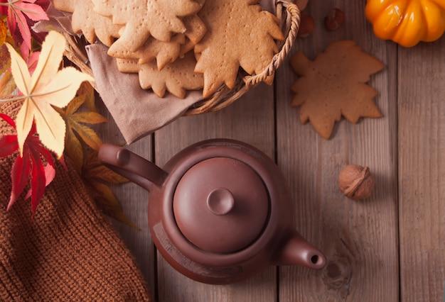 Bule de chá marrom, folhas de outono, biscoitos, abóbora na mesa de madeira