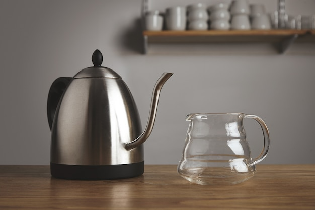 Bule de chá metálico moderno com bule transparente para café filtrado em mesa de madeira grossa em lanchonete