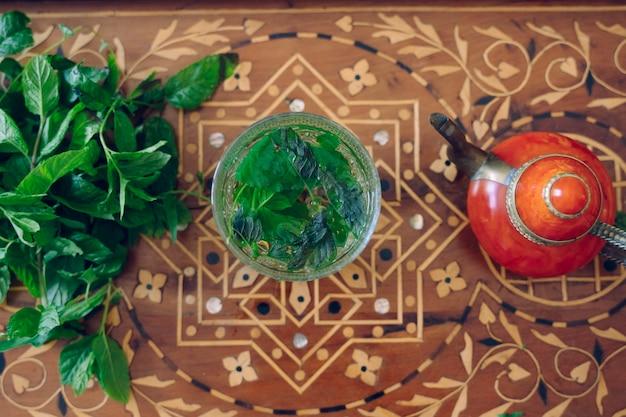 Bule de chá mourisco prata e folhas de hortelã fresca