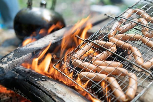 Bule de chá sauasge grelhado fogueira na natureza piquenique fogueira preparando alimentos caminhada na floresta