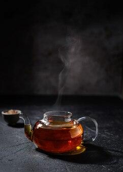 Bule de chá transparente com chá em um fundo escuro