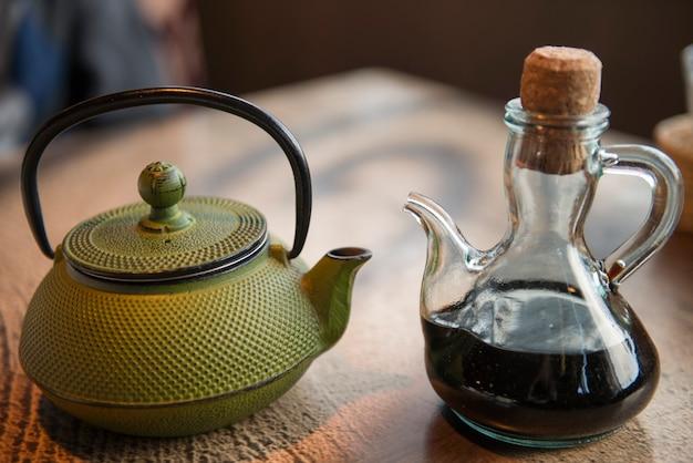Bule de chá verde na mesa de madeira e pote de soja na mesa do café