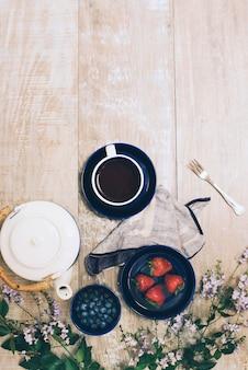 Bule de chá; xícara de café; bagas; garfo com guardanapo e flores no pano de fundo texturizado de madeira