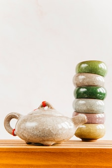 Bule de chinês tradicional com empilhado de xícaras de chá na mesa de madeira