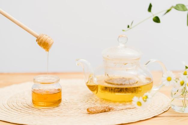 Bule de cristal vista frontal e dipper mel sobre jar