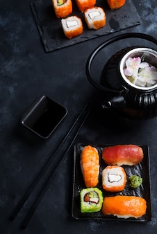 Bule de ferro preto e sushi situado na placa de xisto na mesa de pedra preta, plana leigo