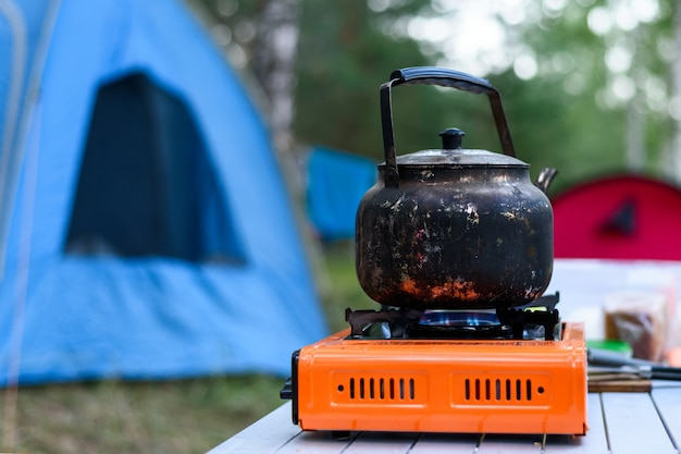 Bule de ferro queimado em um queimador de gás no fundo de uma tenda na natureza, café da manhã no acampamento