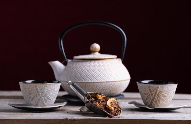 Bule de porcelana branca e dois copos para servir o chá com palin picante