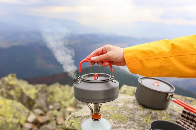 Bule de viagem de acampamento e xícaras de chá de acampamento nas montanhas dos cárpatos