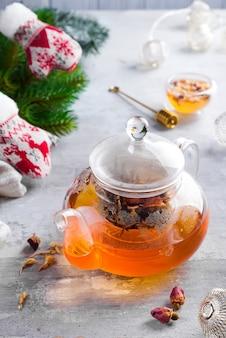 Bule de vidro com chá de flores amarradas, chá quente em bule de vidro e mel com vara de metal mel
